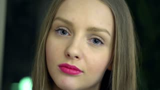 Blonde girl with pink lips doing pensive look to the camera