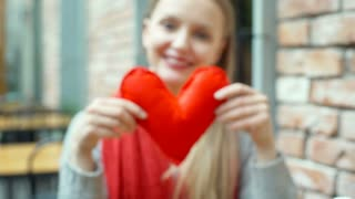 Blurred girl holding handmade heart and showing it to the camera