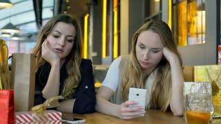 Bored girls sitting in the festive cafe, steadycam shot