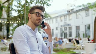 Bored man mimic the person he speaks to through cellphone in the outdoor cafe