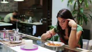 Bored woman eating dinner, man cleaning kitchen