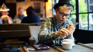 Boy adds sugar to the coffee and mixing it in the cafe