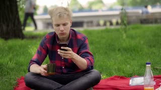 Boy drinking juice and texting on smartphone in the park
