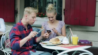 Boy eating meal in the cafe and his girlfriend using smartphone