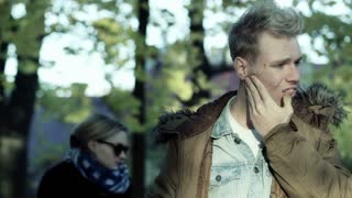 Boy having a toothache and massage his cheek in the autumnal park