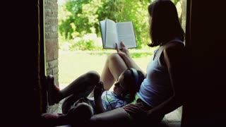Boy listening music on headphones and his mother reading a book