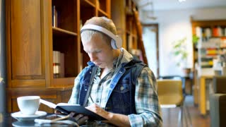 Boy listening music on headphones while reading book in the library