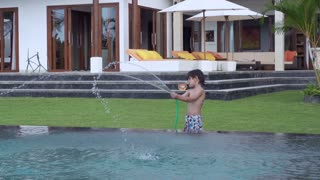 Boy playing with hose in the garden, slow motion shot at 240fps