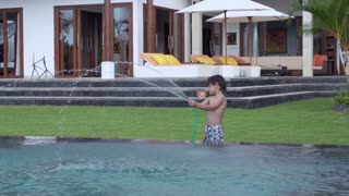 Boy playing with hose in the garden, slow motion shot