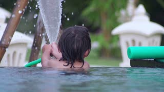 Boy playing with hose in the pool, slow motion shot at 240fps