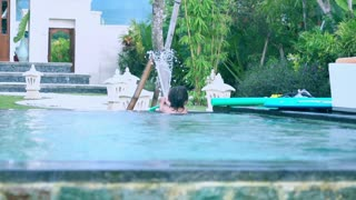 Boy playing with hose in the pool, slow motion shot