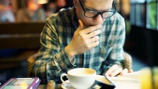 Boy reading a book and drinking coffee in the cafe, steadycam shot