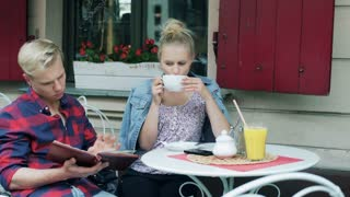 Boy reading menu and girl drinking coffee in the cafe