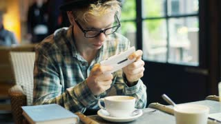 Boy sitting in the cafe and playing game on smartphone