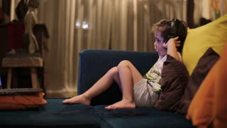 Boy sitting on sofa and looking on laptop, steadycam shot