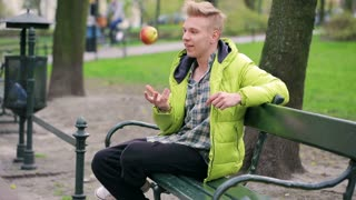 Boy sitting on the bench and throwing apple in the air