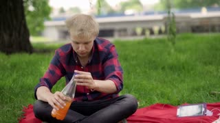 Boy sitting on the blanket in the park and drinking juice