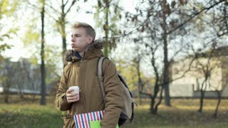 Boy standing in the autumnal park with coffee and his notebook