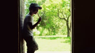 Boy standing in the doors with the view on garden and eating snack