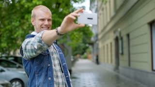 Boy standing on the pathway in the city and doing selfies on smartphone