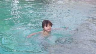 Boy swimming in the pool and waving hand, slow motion shot at 240fps