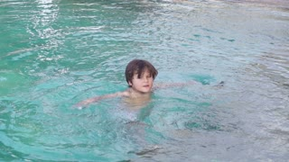 Boy swimming in the pool and waving hand, slow motion shot