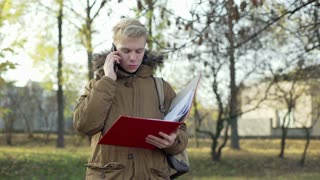 Boy talking on cellphone and holding red binder in the autumnal park