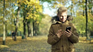 Boy using smartphone in the autumnal park and smiling to the camera
