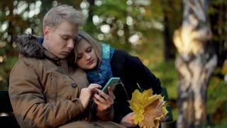 Boy using smartphone in the park and relaxing with his girlfriend