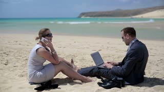 Business couple sitting on the beach and relaxing after work