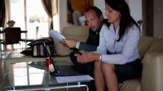 Business couple talking on cellphone and working with laptop in their apartment