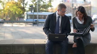 Business couple working with laptop and documents in the city, steadycam shot
