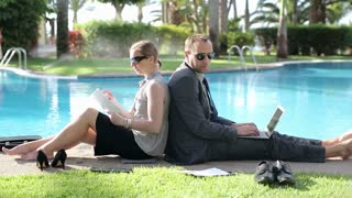 Business couple working with together by the swimming-pool
