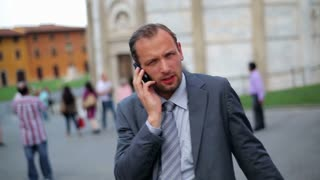 Business man in tourist city talking on his cell phone