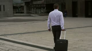 Business person walking with suitcase, slow motion shot at 240fps, steadycam
