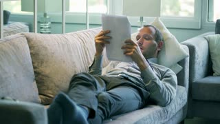 Businessman analyze results and lying on the sofa