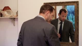 Businessman applying eye cream in front of mirror