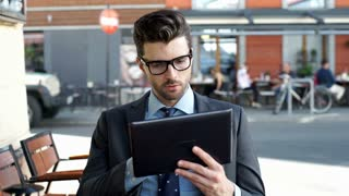 Businessman browsing internet on tablet and smiling to the camera, steadycam sho