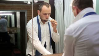 businessman brushing his teeth and looking in the mirror