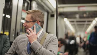 Businessman chatting on cellphone in the subway, steadycam shot