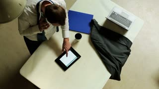 businessman checking data in tablet and talking on the phone
