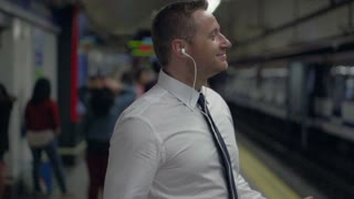 Businessman dancing on metro station, slow motion shot at 240fps, steadycam shot
