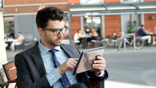 Businessman doing serious look to the camera while browsing internet on tablet