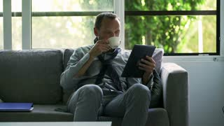 Businessman drinking coffee and browsing internet on tablet at home