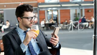 Businessman drinking orange juice while browsing internet on smartphone