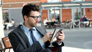 Businessman drinking orange juice while browsing internet on tablet