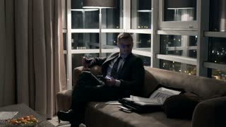 Businessman drinking wine and using cellphone on the sofa at night