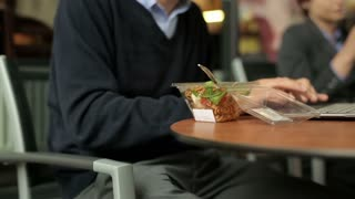 Businessman eating lunch in cafe, outdoor