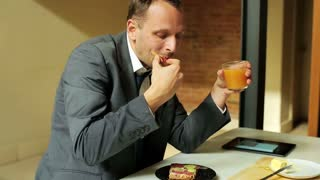 businessman eating sandwich and drinking juice