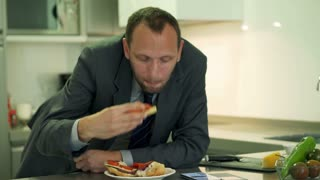 Businessman eating sandwich and using cellphone in the kitchen, steadycam shot